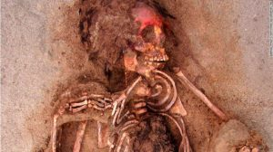 """This May 10, 2011 handout photo provided by National Geographic shows how the face of this child was painted with a red cinnabar-based pigment, at the Huanchaquito-Las Llamas site near Trujillo, Peru. Archaeologists hypothesize that the chest was cut open to remove the heart as part the sacrificial ceremony. """"Skeletal evidence clearly indicates that the children and camelids were sacrificed by cutting open the thoracic cavity,"""" the researchers reported. (Gabriel Prieto/National Geographic via AP)"""