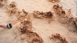 """This April 22, 2011 handout photo provided by National Geographic shows more than a dozen bodies preserved in dry sand for more than 500 years, at the Huanchaquito-Las Llamas site near Trujillo, Peru. Researchers reported that, """"except for three adult burials (two females and one male), all the human skeletal remains were of children, ranging in age from approximately five to fourteen years, with the majority falling in the range of eight to twelve years of age."""" (Gabriel Prieto/National Geographic via AP)"""